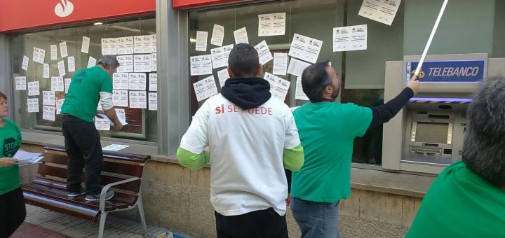 Membres de la PAH Maresme Nord enganxant cartells al Santander aquest matí
