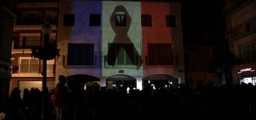 Projecció de la bandera francesa i crespó negre a la façana Ajuntament