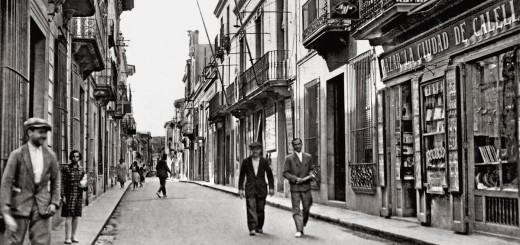 """Postal del carrer de l'església a principis dels 30. S'hi veu el Bazar Ciudad de Calella, """"la papelera""""."""