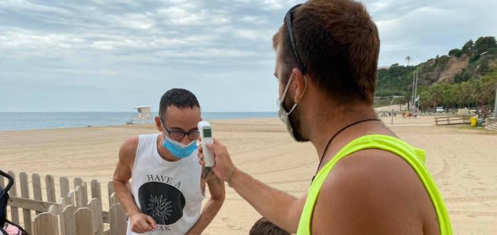 Monitor de les activitats de lleure a la platja prenent la temperatura a un usuari, seguint el protocol de seguretat