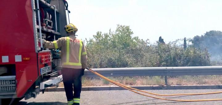 Bombers treballant en l'extinció d'un petit foc al voral de l'autopista C-32 nord, a Premià de Dalt